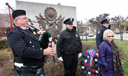 Bagpiper Frank Stasa III, Birmingham Police Officers Stefan Syts and Brent Macumber lay a wreath at the World War II monument with Jan Stafford, regent of the Piety Hill Chapter of the Daughters of the American Revolution.
