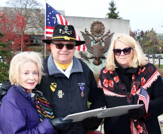 DAR Piety Hill regent Jan Stafford of Bloomfield Township (left) and chair of the event Lisa Milton of Bloomfield Township, review program details with Vietnam veteran Tom Stempka, of Bloomfield Hills.