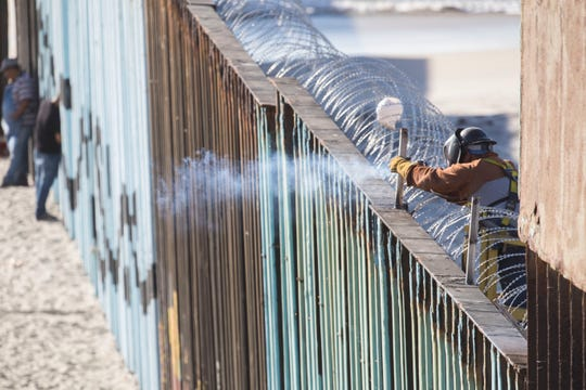 A welder in the U.S. side of the wall in Playas de Tijuana neighborhood in Tijuana, Mexico sets up infrastructure for serpentine wire as migrants have arrived.