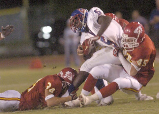 Nick Xalis (45) makes a tackle during the game between Palm Desert and Los Altos High School in 2004.