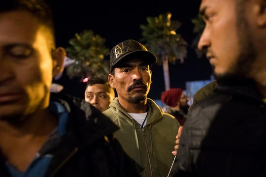 """Honduran immigrants look on as Mexican residents of Playas De Tijuana confronted the migrants who had set up a makeshift camp at """"Friendship Park"""" in Playas De Tijuana. The Mexican residents demanded that the the migrants leave the area and threaten the migrants if they did not leave. Federal and Municipal Mexican police kept both groups separated and some incidents of violence broke out throughout the night."""