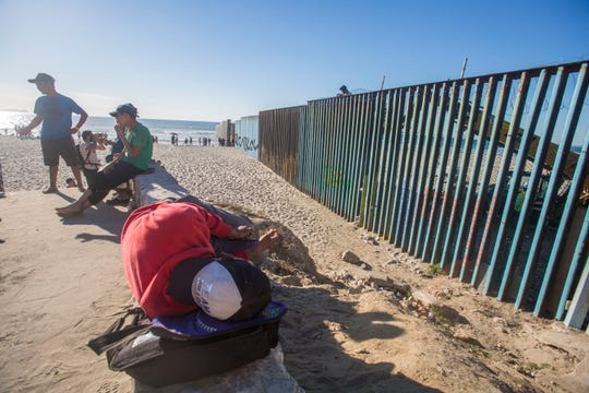 Migrants have begun arriving in Tijuana and have opted to camp out in Playas de Tijuana neighborhood in Tijuana, Mexico. In this photo, a young man scales the wall. In the background a welder is seeing putting up serpentine wire on the wall.