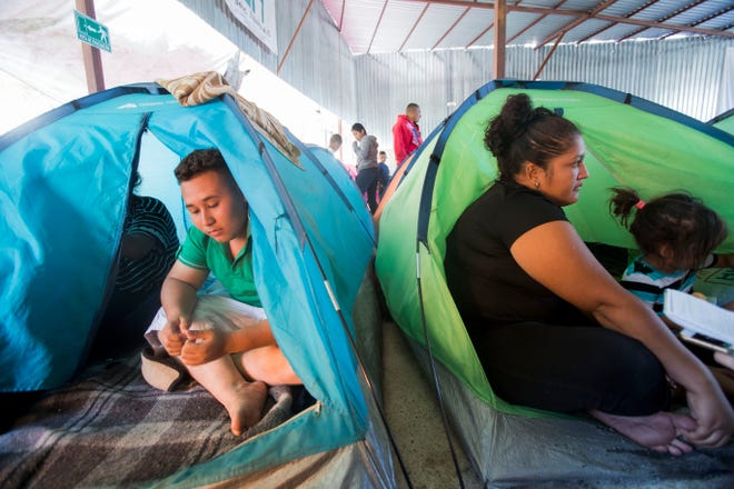 At left, Joel Lopez, 19,  and his cousin, at right, Belkis Bustamante, 23, and her daughter Chisty Garcia, 4, rest at a migrant shelter in Tijuana, Mexico after having arrived 30 days after leaving on foot from Honduras.
