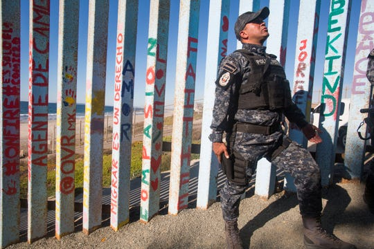 A Mexican Federal Police officer tells young migrants to settle down as he puts his hand on his weapon. Migrants have begun arriving in Tijuana and have opted to camp out in Playas de Tijuana neighborhood in Tijuana, Mexico. In this photo, a young man scales the wall.