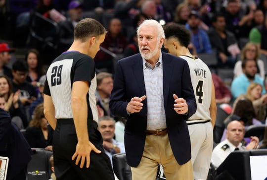 Spurs coach Gregg Popovich discusses a call with referee Mark Lindsay during a game against the Kings on Nov. 12 at Golden 1 Center.