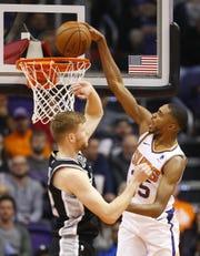 Suns rookie forward Mikal Bridges dunks over Spurs forward Davis Bertans during a game at Talking Stick Resort Arena.