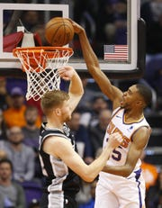 Phoenix Suns forward Mikal Bridges (25) scores a basket while being guarded by San Antonio Spurs forward Davis Bertans (42) during a NBA game at Talking Stick Arena in Phoenix on November 14.