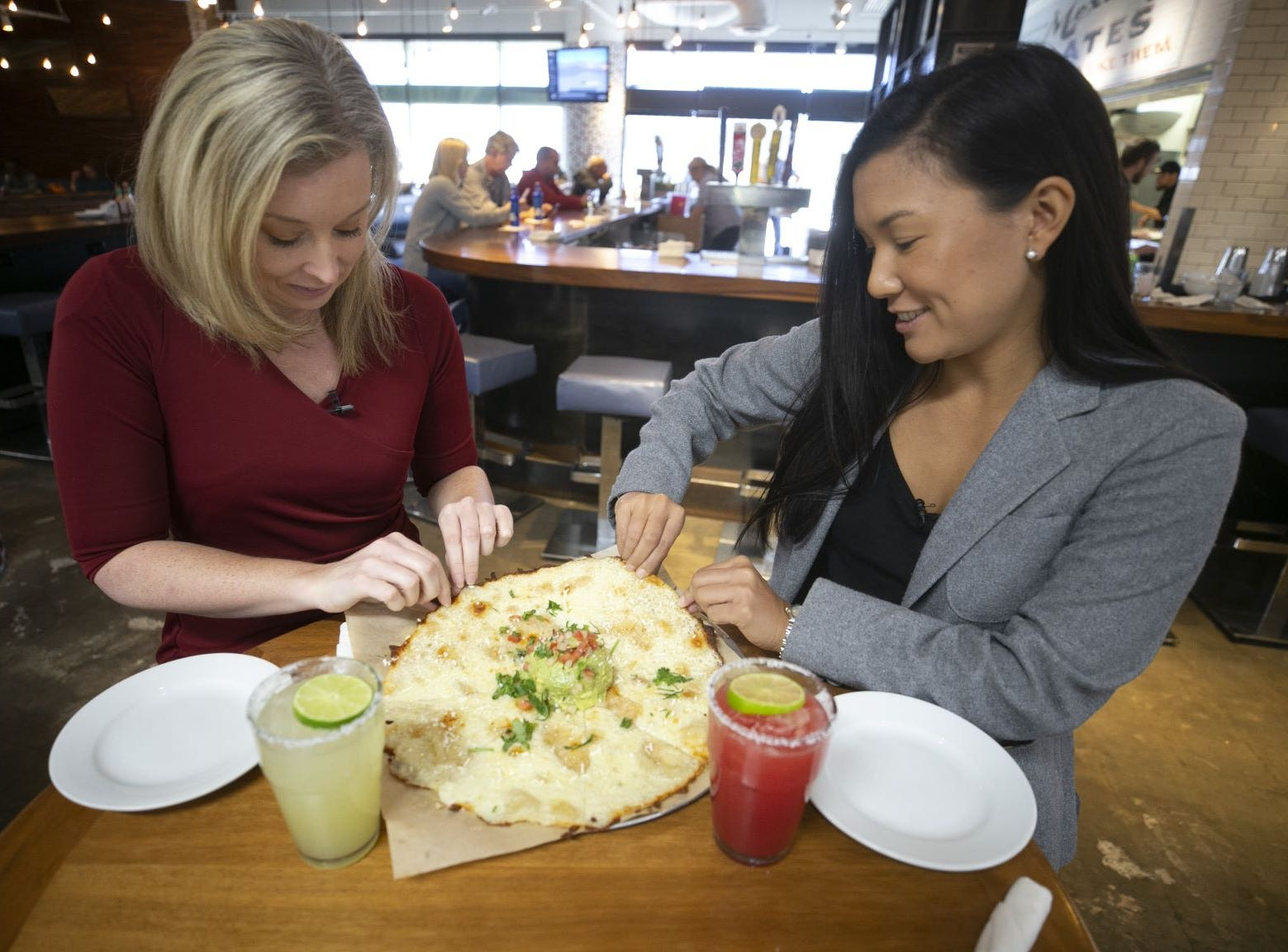 Melissa Yeager, (left) Arizona Republic and azcentral consumer and travel reporter and Lauren Saria, Arizona Republic and azcentral food and dining reporter taste the Cheese Crisp at Blanco Tacos in Terminal Four of Phoenix Sky Harbor International Airport on Tuesday, November 13, 2018.