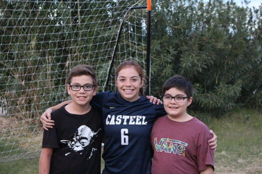 Scarlett Frohardt is surrounded by her twin biological brothers Cooper and Cannon, right, on Nov. 14.