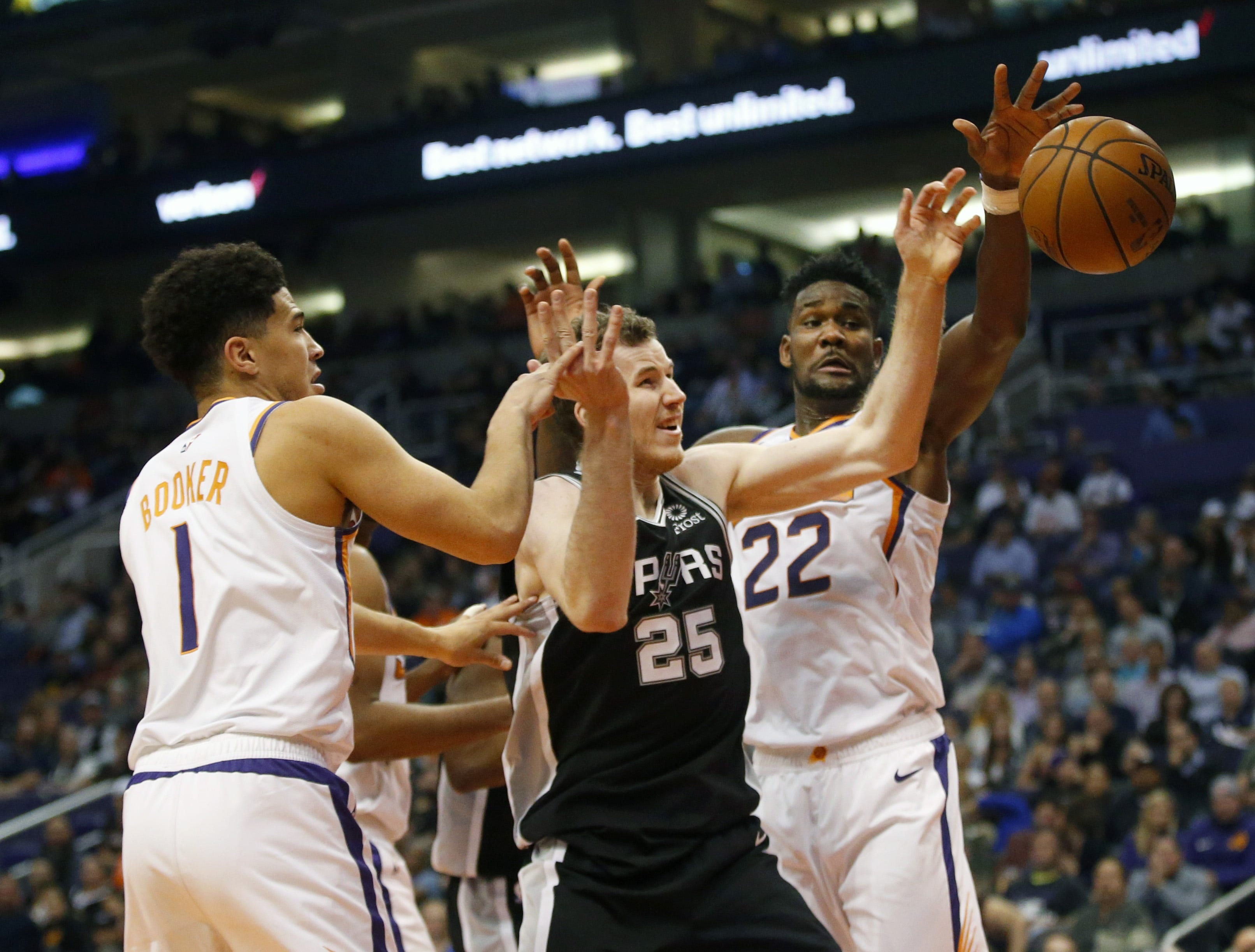 Phoenix Suns guard Devin Booker (1) and center Deandre Ayton (22) battle San Antonio Spurs center Jakob Poeltl (25) for the ball during a NBA game at Talking Stick Arena in Phoenix on November 14.