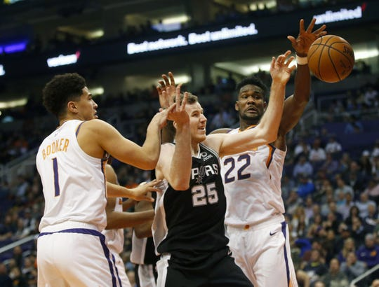 Suns guard Devin Booker and center Deandre Ayton battle for a loose ball with Spurs center Jakob Poeltl during a game Nov. 14 at Talking Stick Resort Arena.