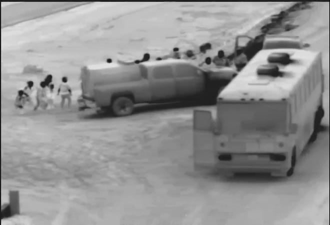 Border Patrol agents lead a group of migrants to buses in order to be transported to the station and processed after crossing the border illegally near Yuma.