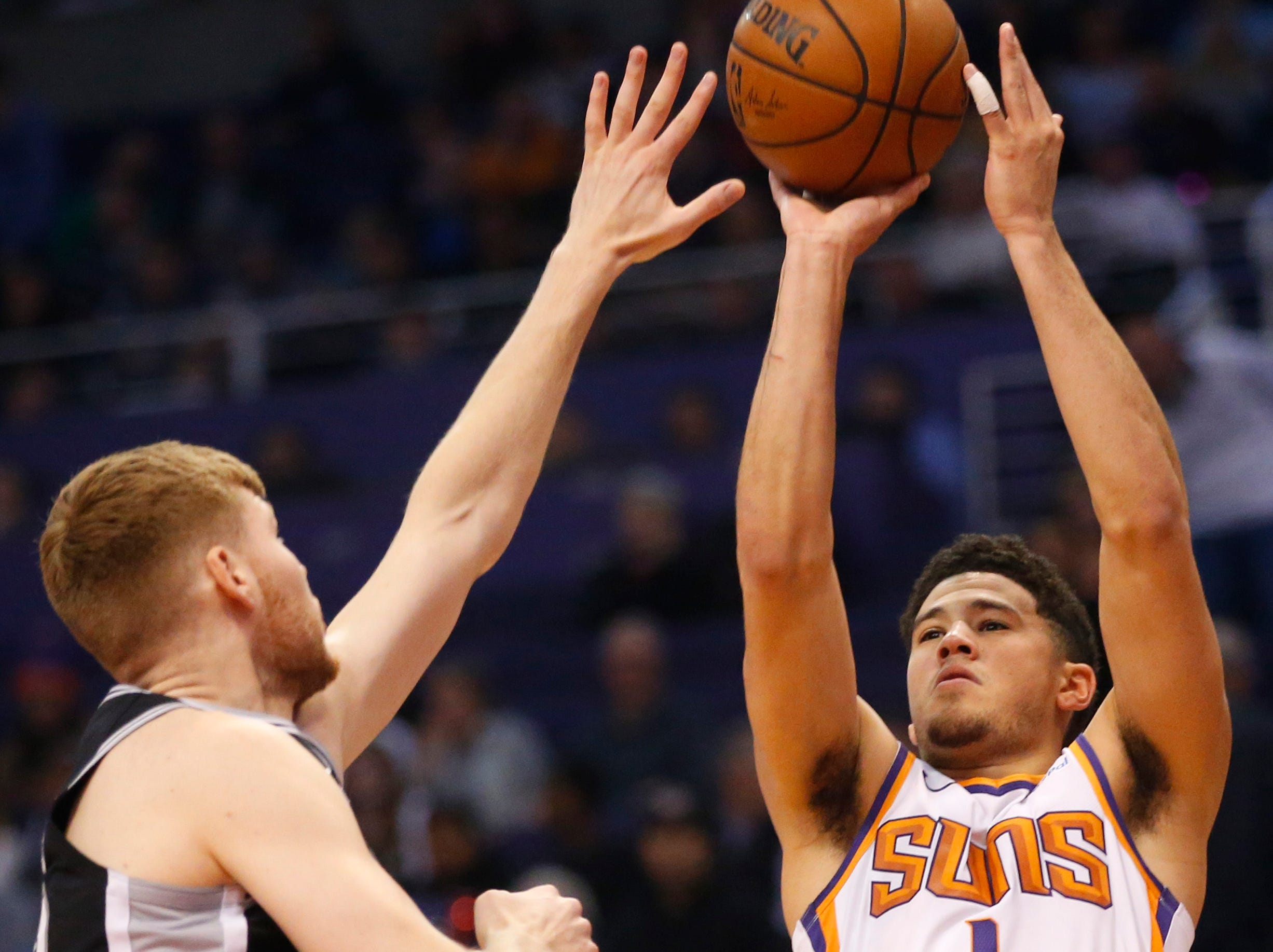 Phoenix Suns guard Devin Booker (1) takes a shot while being guarded by San Antonio Spurs forward Davis Bertans (42) during a NBA game at Talking Stick Arena in Phoenix on November 14.
