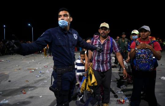 Un policía coordina la llegada de migrantes.