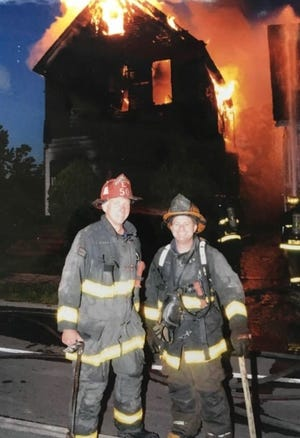 Michael Lubig, right, is seen at a house fire in Detroit.