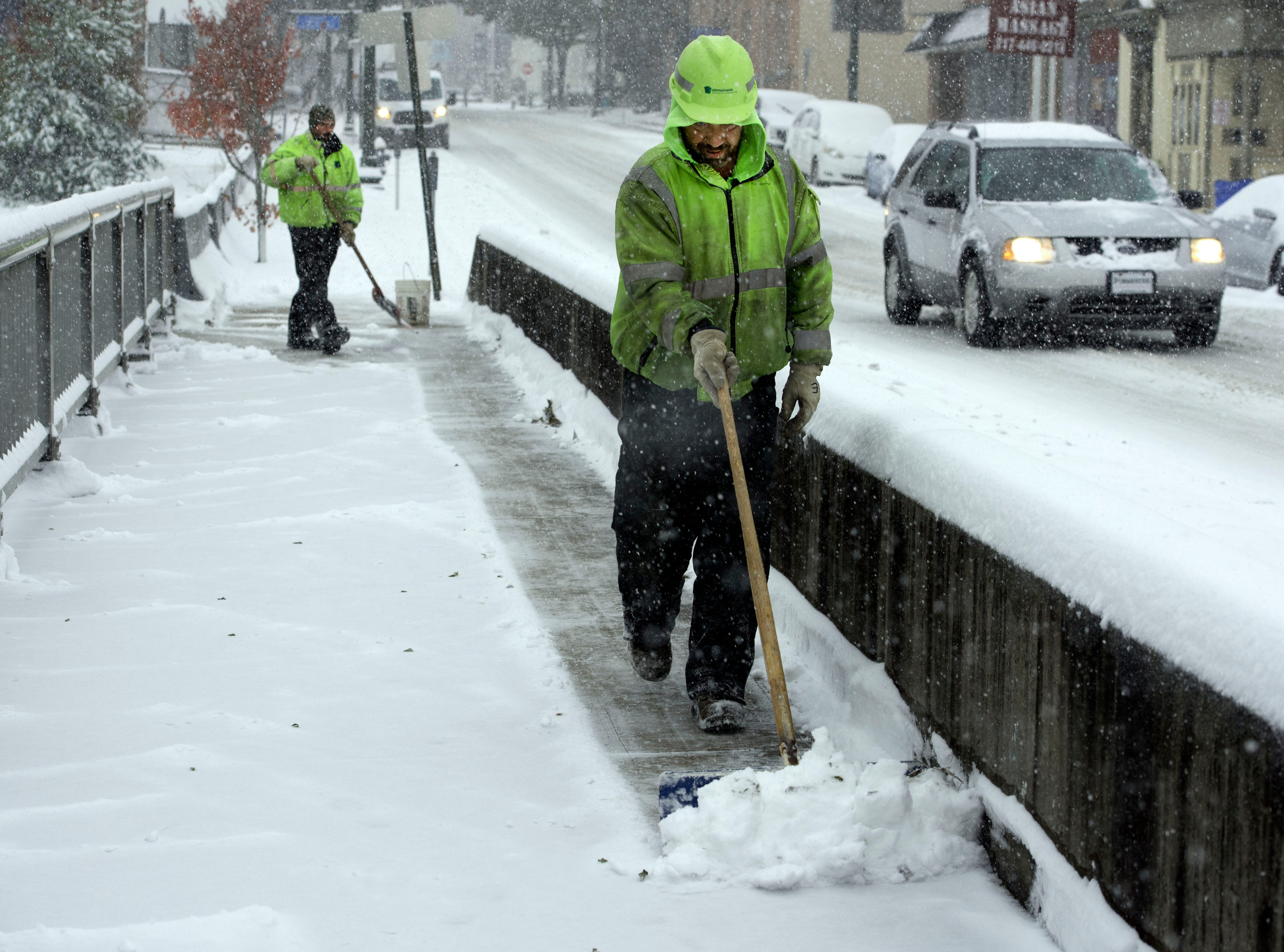 PennDOT employees clear snsow off bridge sidewalks along Lincoln Way East, Chambersburg. A winter storm hit Franklin County on Thursday morning, November 15, 2018.