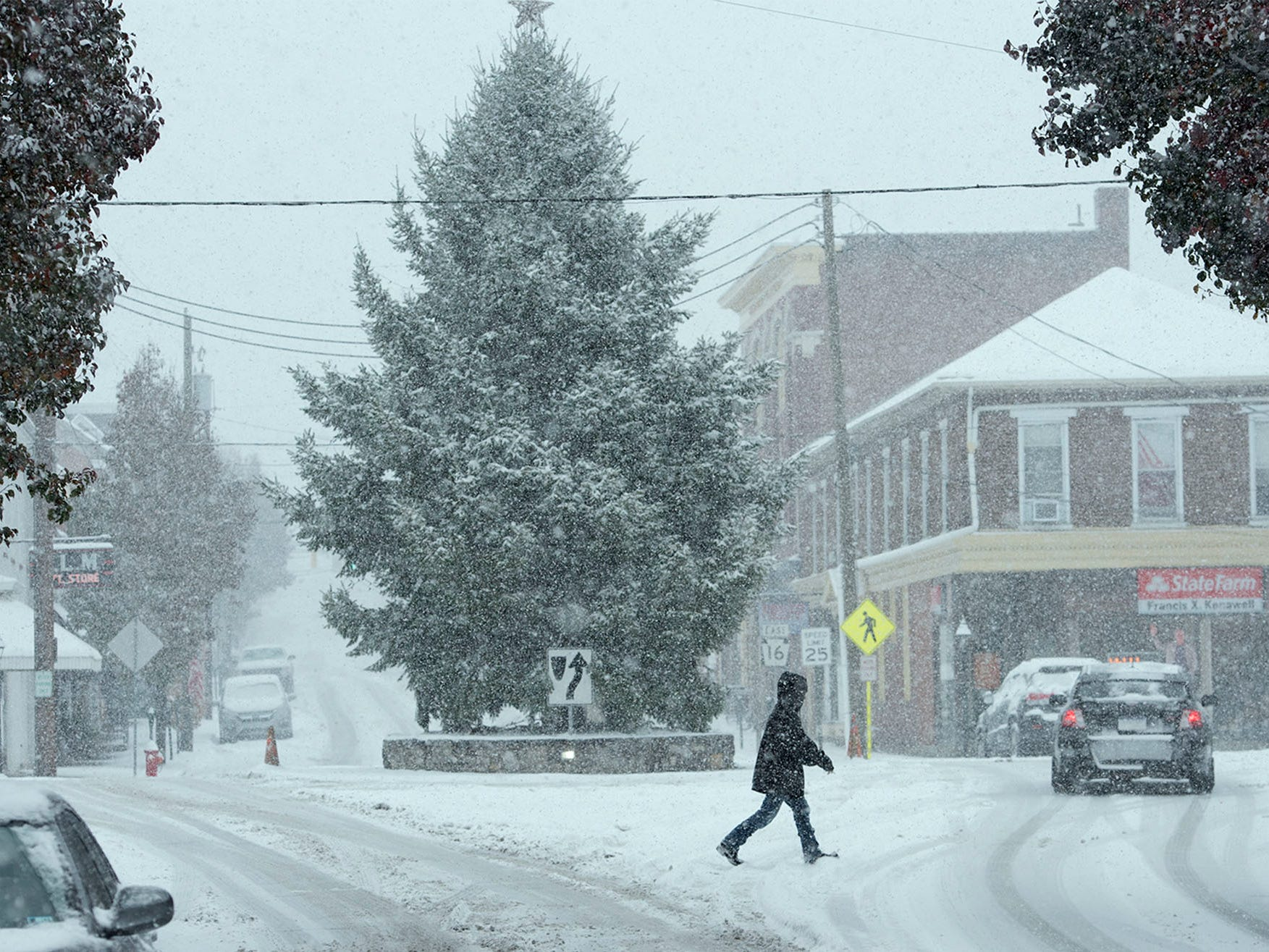 A pedestrian crosses the street in front of the Greencastle Christmas tree. Snow started in Franklin County on Thursday morning, November 15, 2018.