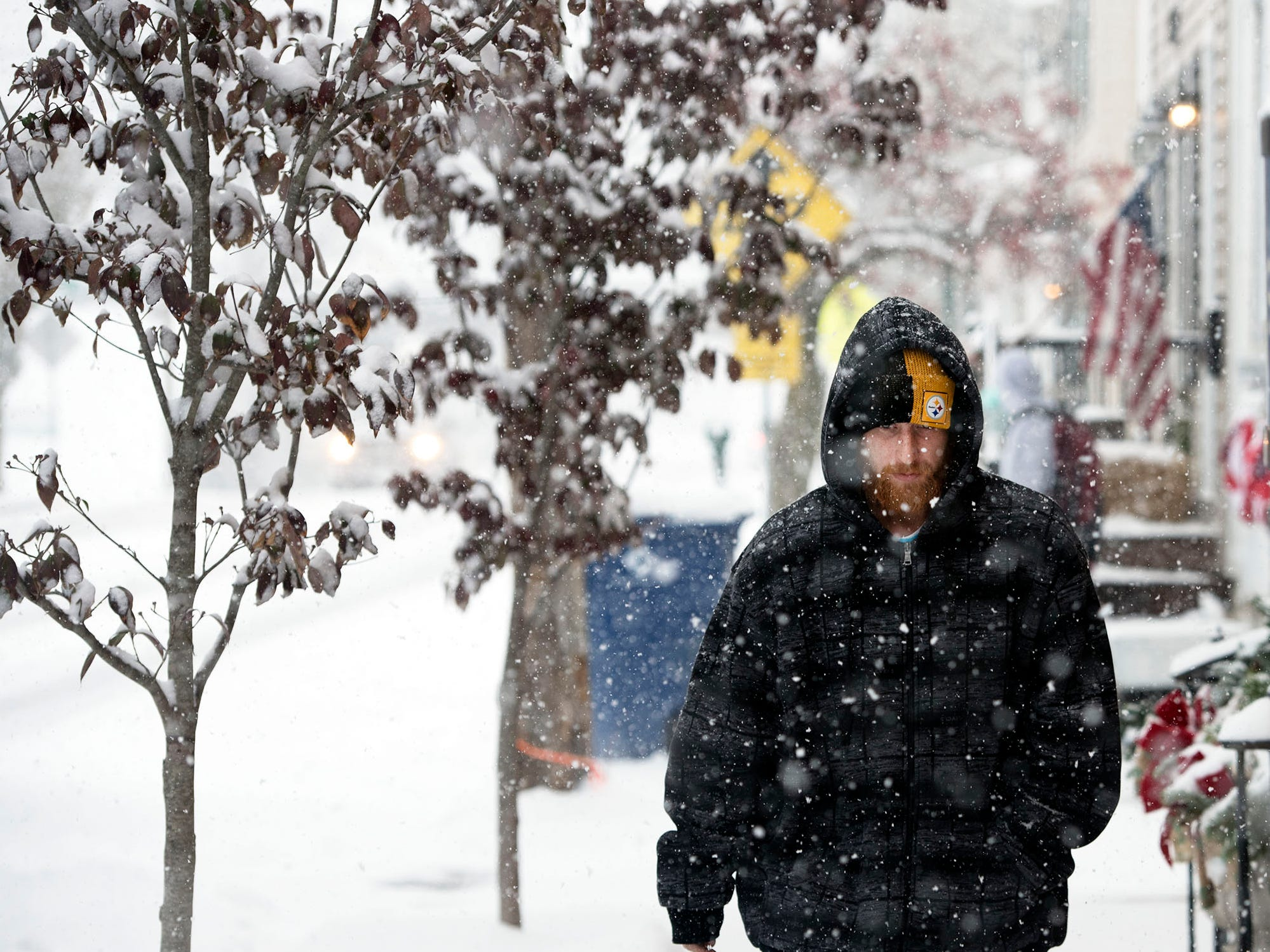 Cody Fittry walks along a snowy sidewalk in Greencastle. Snow started in Franklin County on Thursday morning, November 15, 2018.