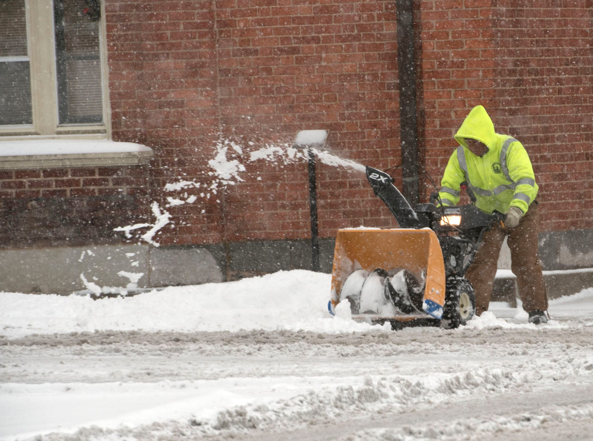 A worker clears snow off sidewalks in Chambersburg. A winter storm hit Franklin County on Thursday morning, November 15, 2018.