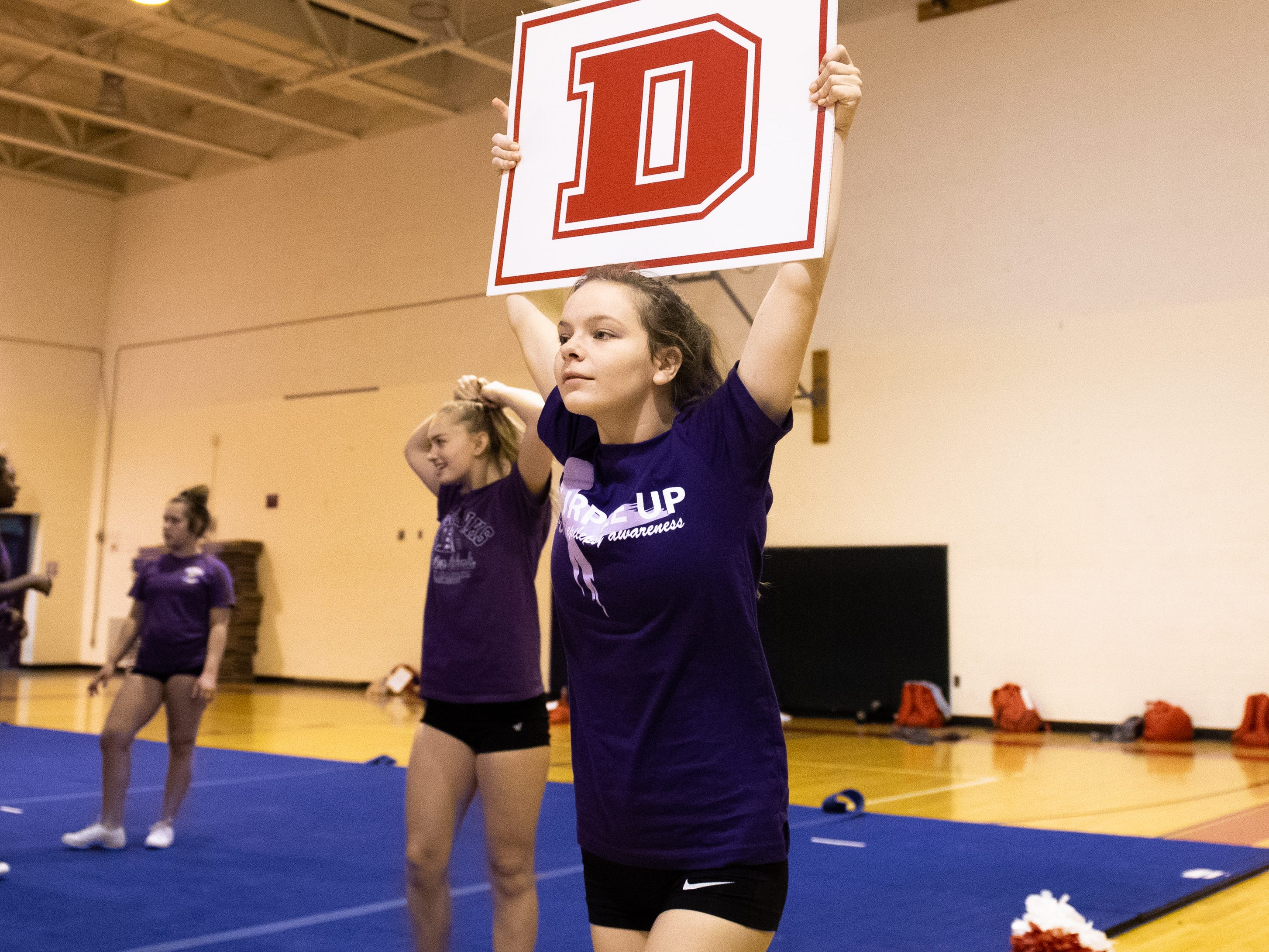 Abby Reiber holds up a letter during Dover's competitive spirit practice, November 14, 2018.