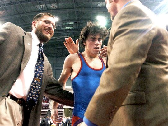 Tony Miller celebrates with wrestler Brian Polashuk in 2006 after Polashuk won an individual state title at 125 pounds. Miller has coached 14 state medalists in his time at Spring Grove