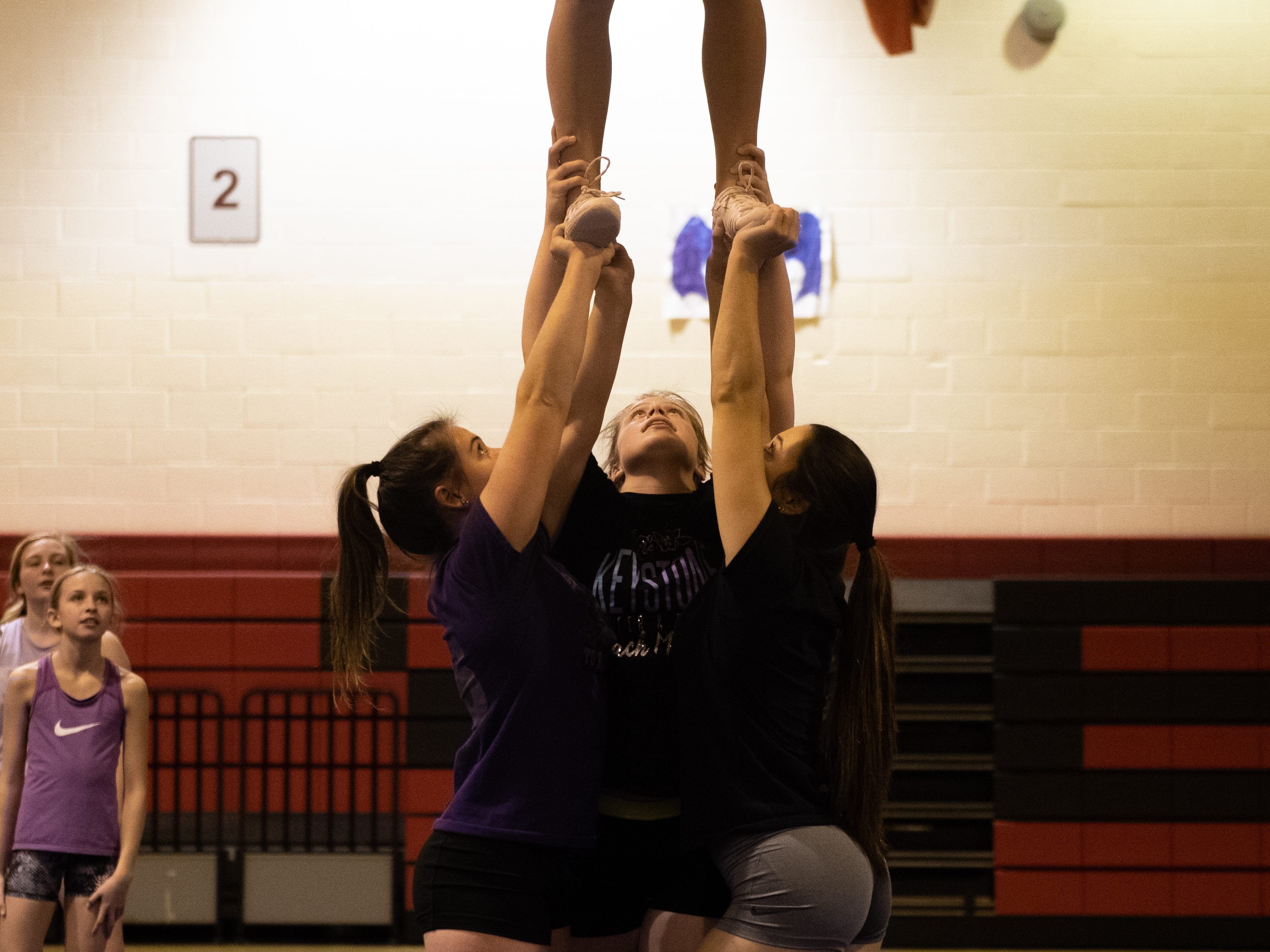 Dover's base holds up their teammate during competitive spirit practice, November 14, 2018.