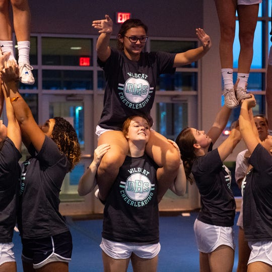 Abrianna Gentile waves while on the shoulders of Maddie Hermin during Dallastown's competitive spirit practice, November 14, 2018.