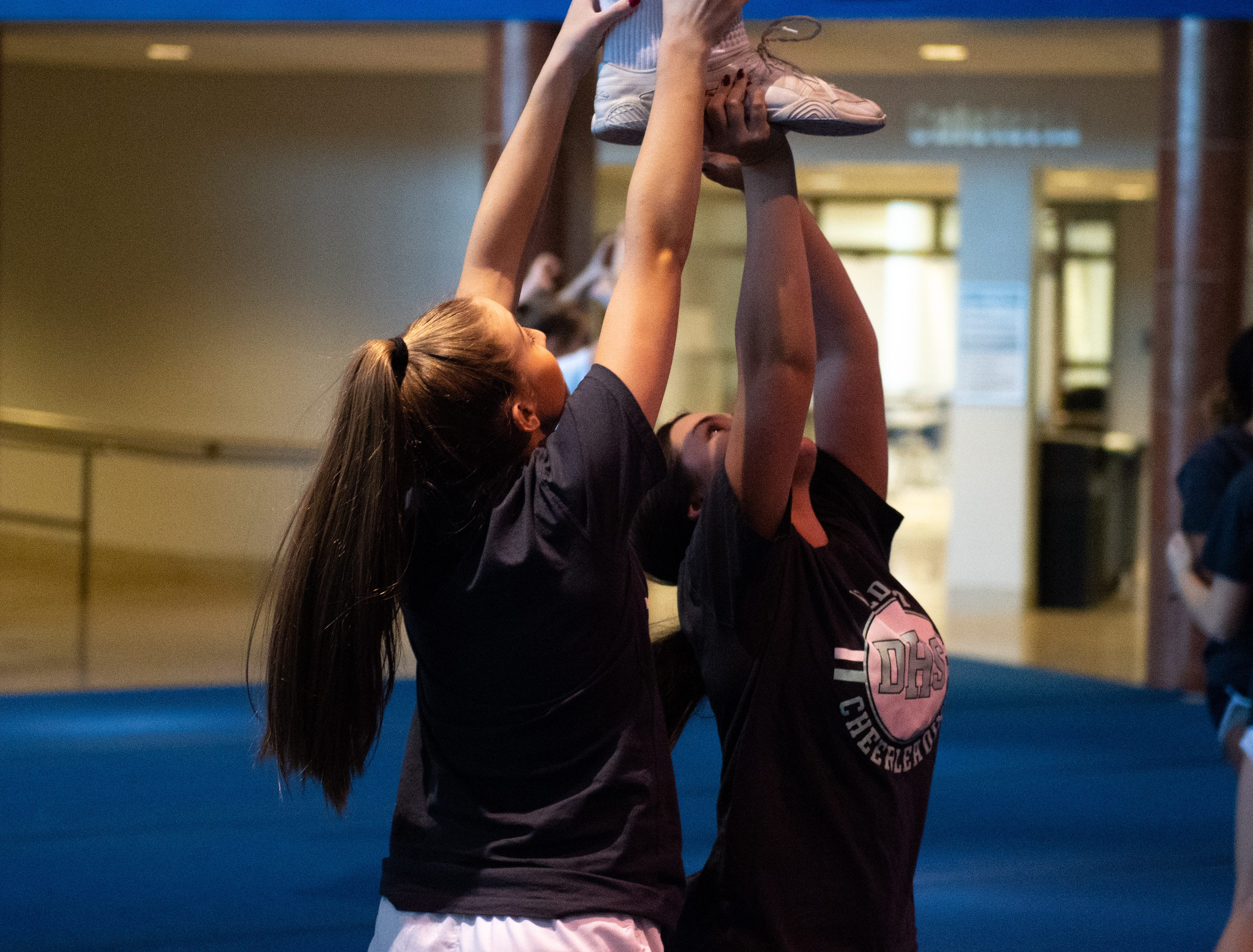 The squad members on the bottom hold up their teammate during Dallastown's competitive spirit practice, November 14, 2018.
