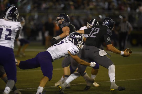 Damonte Ranch's Cade McNamara (12) escapes pressure while taking on Spanish Springs during their football game in Reno on Sept. 7, 2018.