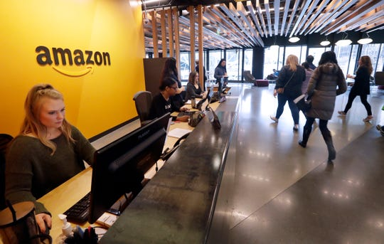 Employees walk through a lobby at Amazon's headquarters Tuesday, Nov. 13, 2018, in Seattle. Amazon, which is growing too big for its Seattle hometown, is spreading out to the East Coast.