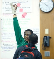 Eighth-grader Abdul Aden gets a student's attention during English class at Nathaniel Rochester Community School.