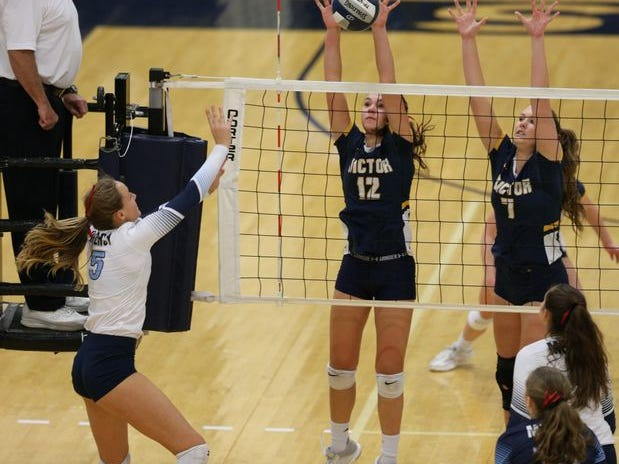 Victor's Emma Werkmeister (120 and Makenzie Bills set up a block at the net against Mercy during the 2018 Section V Class A girls volleyball championship match at Gates Chili.