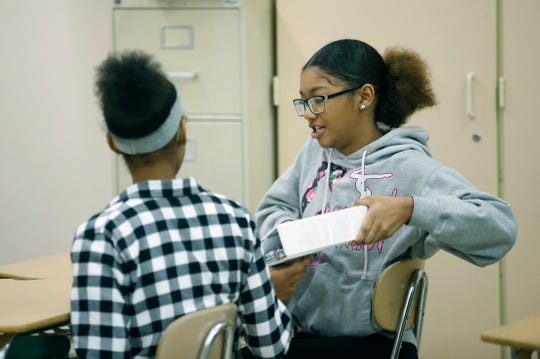 Eighth-grader Tiketa Thomas pulls out a binder during English class at Nathaniel Rochester Community School.