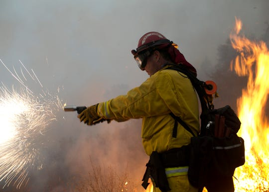 Firefighter Ross Miller fires an incendiary round into a fire line in the Camp Fire as part of a control burn Near Bloomer Hill in Butte County in California on Nov. 14, 2018.