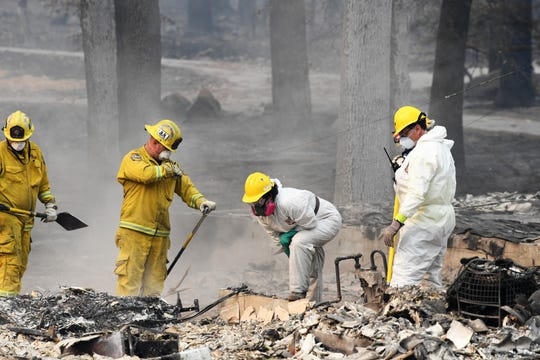 Search and rescue teams on Tuesday, Nov. 13, 2018 comb through rubble looking for the remains of victims killed in the Camp Fire in Paradise, Calif.
