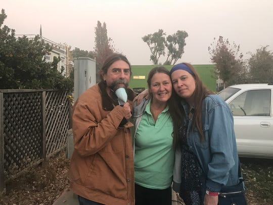 David Heidelberger, 54, and his wife Melanie, 44, evacuated the Camp Fire and are staying at a Red Cross shelter at the Butte County Fairgrounds in Chico with their children. Their friend Corie Hawkins, 54, middle, of Chico drove to see them because for days she didn't know if they'd made it out alive.