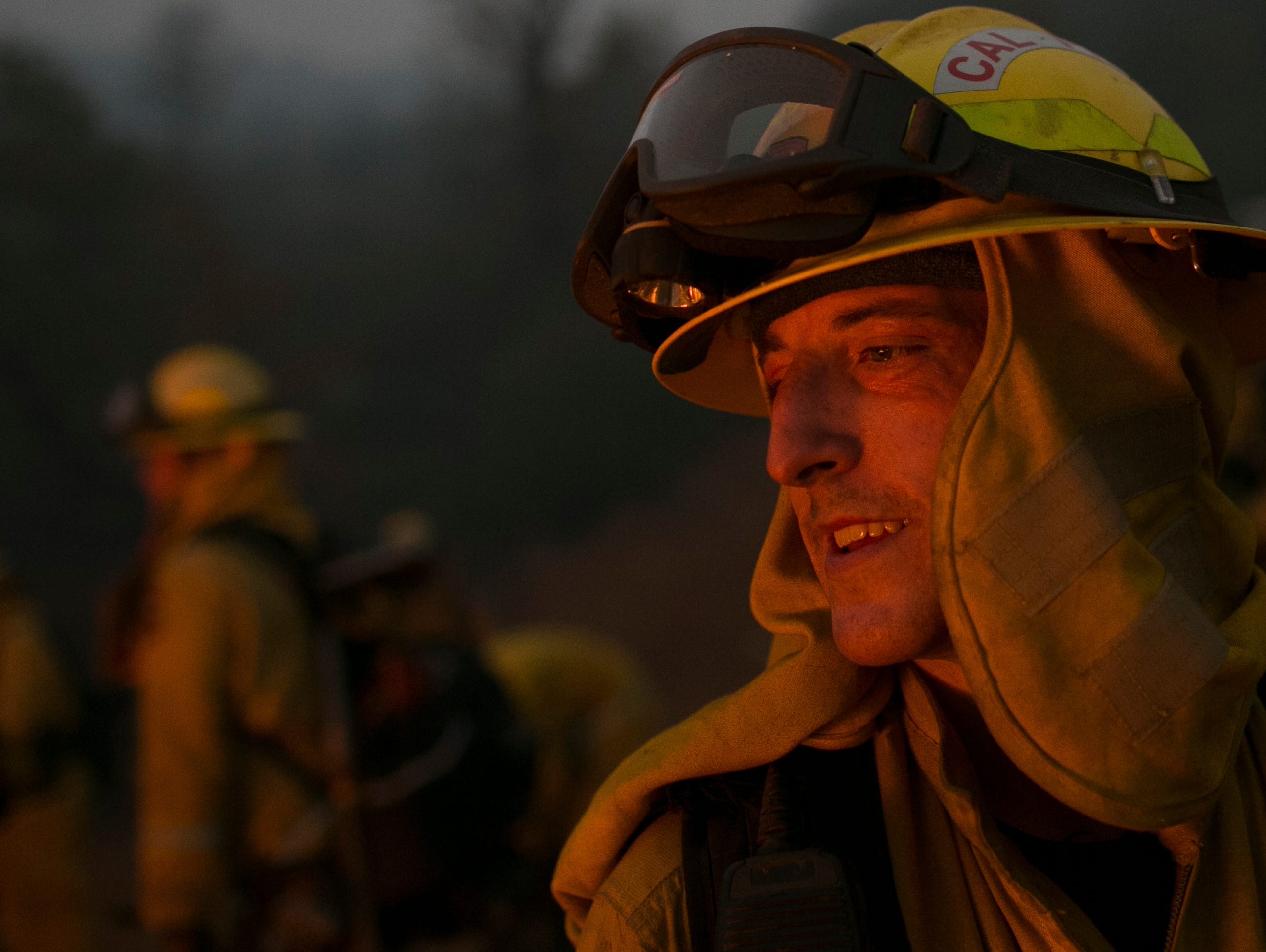 Firefighter Brandon Feller looks into a control burn used to help fight the Camp Fire Near Bloomer Hill in Butte County in California on Nov. 14. 2018. Feller was burned in a fire earlier in the year and after being cleared for medical leave returned to work at the Camp Fire.