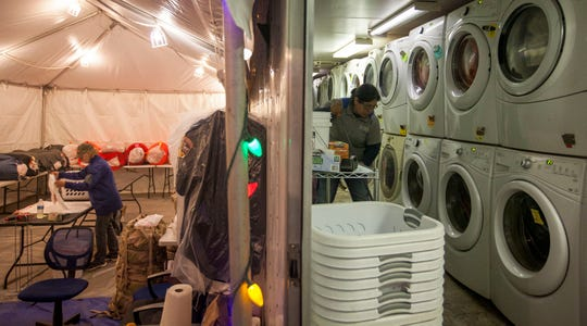 Employees for All American Emergency Services work in the laundry trailer the company was hired to provide for the officials working at the incident command center for the Camp Fire at the Butte County Fairgrounds.(Kelly Jordan)