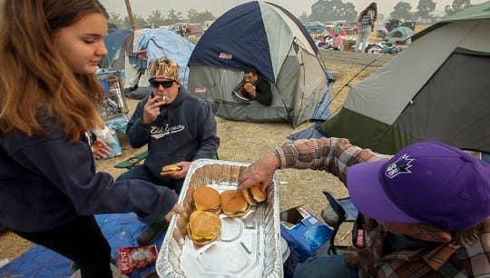 Daryl Merritt, 55, of Paradise, watches as volunteer Hailey Adams, 13, hands out hamburgers at a tent compound in a field next to the Walmart in Chico, CA, Wednesday, November 14, 2018. Merritt has no idea if his home survived the Camp Fire but is making the best of things with new friends and neighbors.