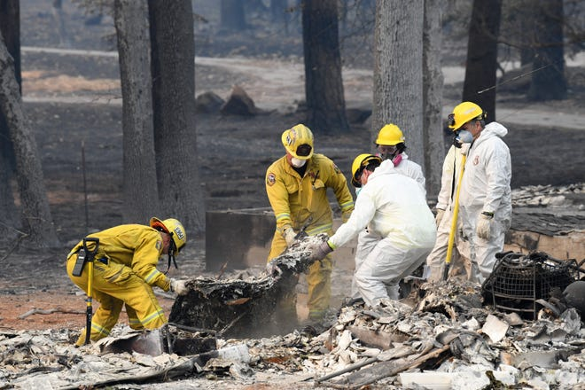 Search and rescue teams on Tuesday, Nov. 13, 2018, comb through rubble looking for the remains of victims killed in the Camp Fire in Paradise.