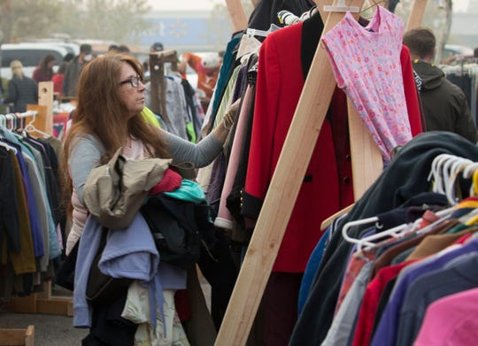 Cindy De Lano, of Paradise, sorts through donated clothing trying to find some items for her and her family to keep warm November 14, 2018. With minutes to evacuate, she left with the clothes on her back.