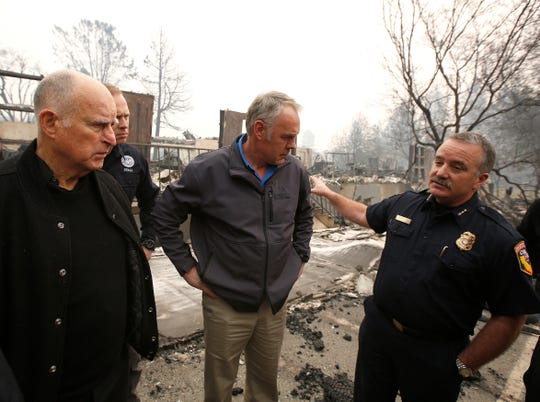 Scott Upton, right, the chief of the Northern Region for the California Department of Forestry and Fire Protection briefs California Gov. Jerry Brown, Federal Emergency Management Agency Director Brock Long, second from left, and U.S. Secretary of the Interior Ryan Zinke, third from left, during a a tour of the fire ravaged Paradise Elementary School Wednesday, Nov. 14, 2018, in Paradise, Calif. The school is among the thousands of homes and businesses destroyed along with dozens of lives lost when the Camp Fire burned through the area last week. (AP Photo/Rich Pedroncelli)