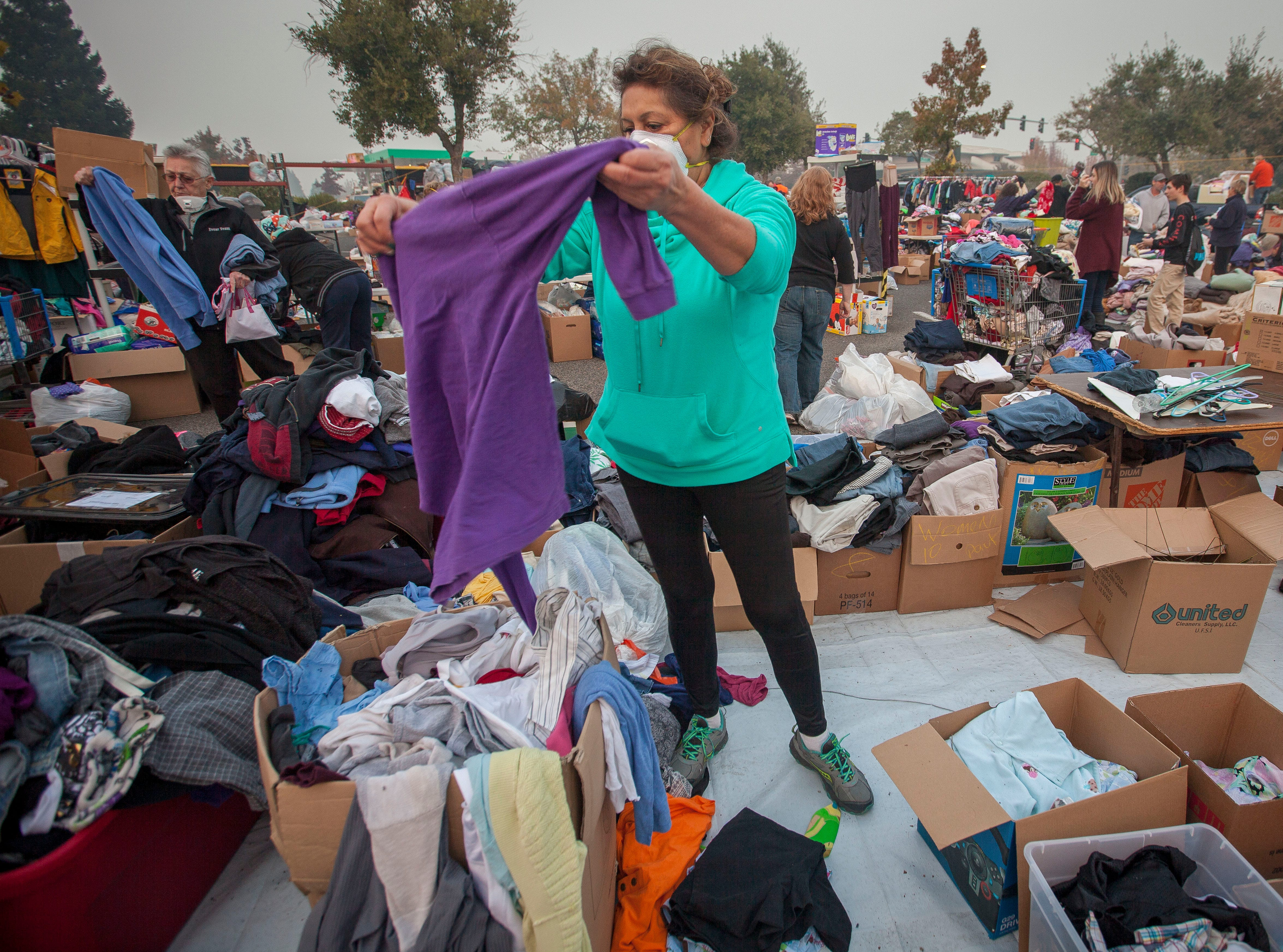 Maria Lewis, a volunteer, folds and sorts boxes of donated  clothing for the people who have taken refuge in the Walmart parking lot in Chico, CA, Wednesday, November 14, 2018. Lewis who lives north of Chico, had the day off and decided she needed to be here helping those who have suffered from the Camp Fire.