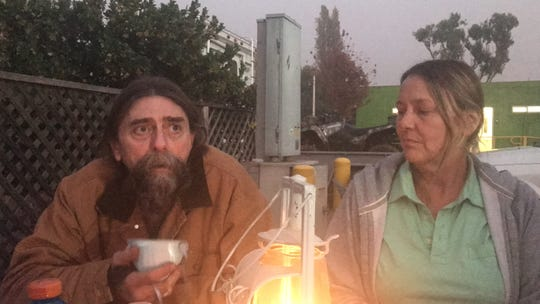 David Heidelberger, 54, sitting next to Corie Hawkins, 54, keeps warm by a lantern, talking about his family's harrowing escape from Magalia during the Camp Fire last week. Heidelberger's emphysema has been exacerbated by the soot-and-smoke-filled air.