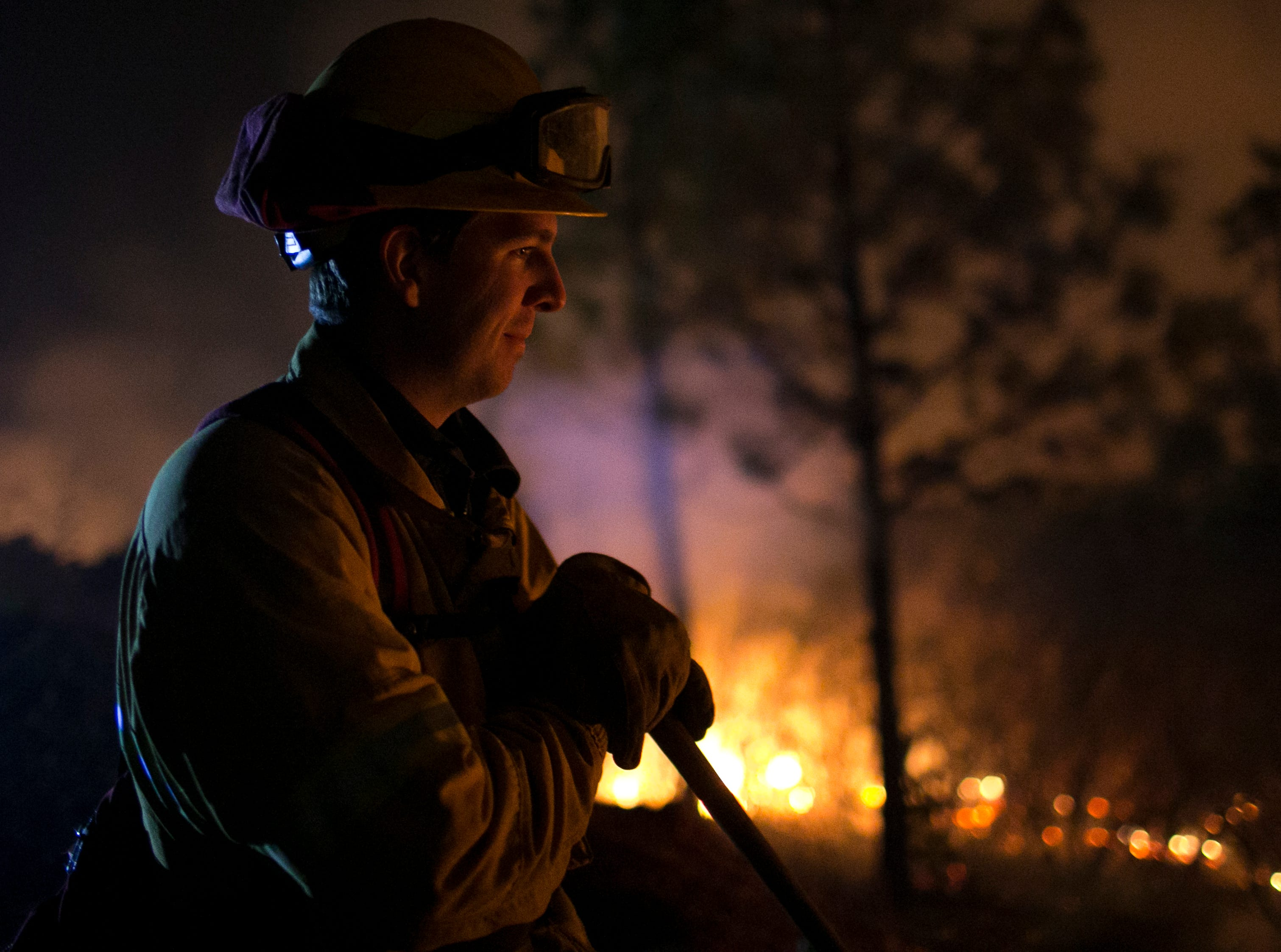 Firefighter Dylan Foster helps hold a line in the Camp Fire with a control burn Near Bloomer Hill in Butte County in California on Nov. 14, 2018.