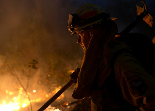 Firefighter Clayton Mazzaglia looks into a control burn used to help fight the Camp Fire Near Bloomer Hill in Butte County in California on Nov. 14. 2018.