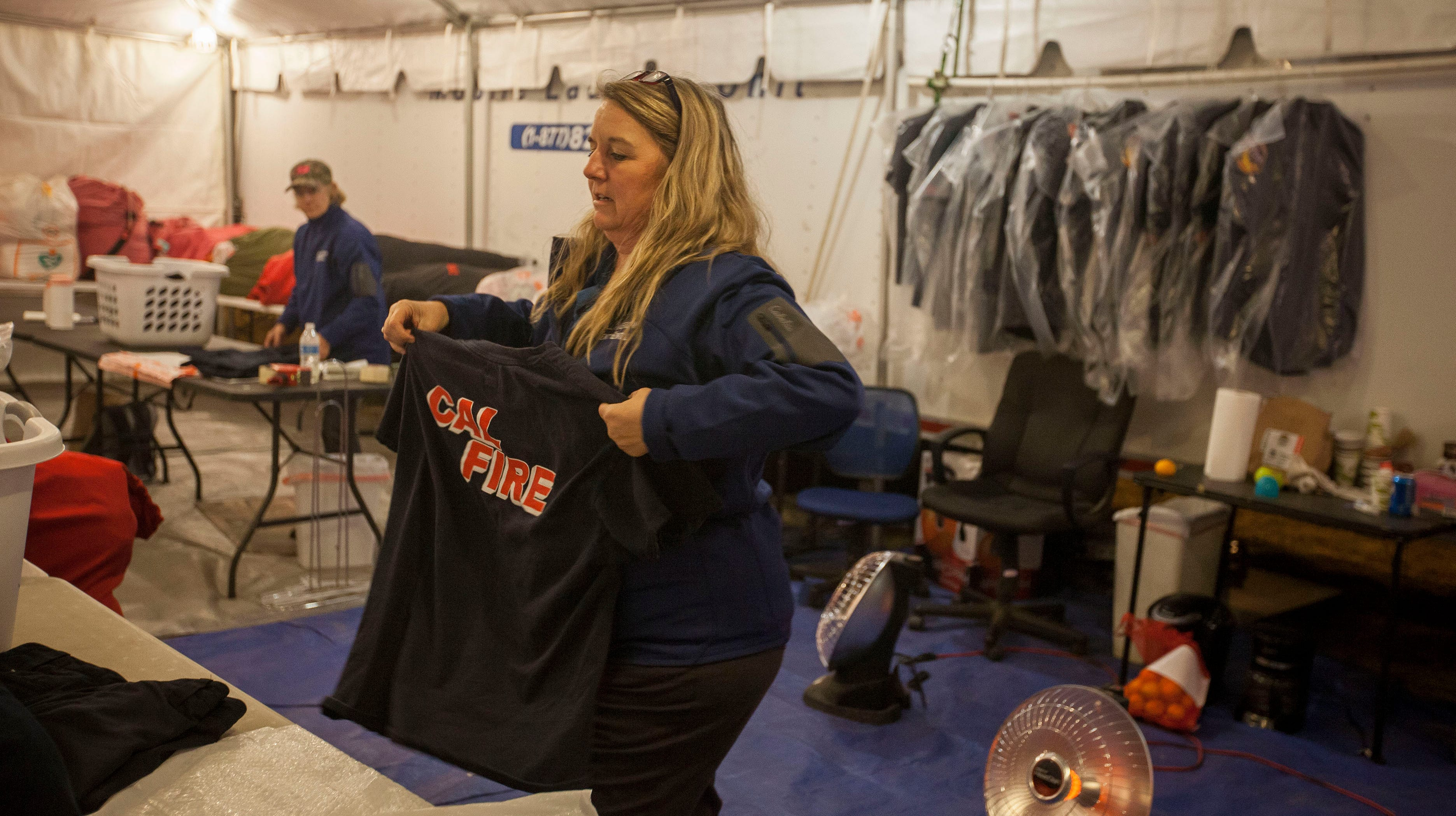 Kelly Daniels, an employee for All American Emergency Services folds shirts from the Cal Fire teams as she works in the laundry trailer that the company was hired to provide for the officials working at the incident command center for the Camp Fire at the Butte County Fairgrounds.(Kelly Jordan)