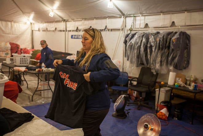 Kelly Daniels, an employee at Corning, California-based All American Tent Emergency Services folds shirts from the Cal Fire teams as she works in her company's laundry trailer. The vendor provided the service at the Camp Fire's  incident command center at the Butte County Fairgrounds in Chico.