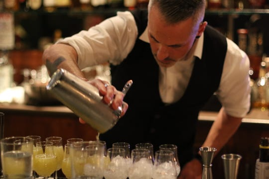 James Lorance pours taster portions of at cocktails competition Brutal Bar on Nov. 5, 2019.