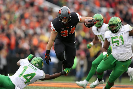 Oregon State's Ryan Nall (34) leaps over Oregon's Ugo Amadi (14) in the first half of the Oregon vs. Oregon State Civil War football game at Oregon State University in Corvallis on Saturday, Nov. 26, 2016.